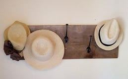 Τρία καπέλα αχύρου στο ξύλινο ράφι καπέλων στον τοίχο Στοκ Φωτογραφία
