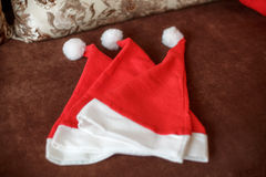 Τρία καπέλα Santa στον καναπέ Νέα οικογενειακή έννοια έτους Στοκ φωτογραφίες με δικαίωμα ελεύθερης χρήσης