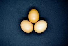 Τρία καφετιά αυγά στο μαύρο υπόβαθρο στοκ φωτογραφίες