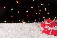 Τρία κιβώτια δώρων στο χιόνι με τα φω'τα Χριστουγέννων στο υπόβαθρο Στοκ φωτογραφίες με δικαίωμα ελεύθερης χρήσης