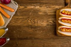 Τρία κλασικά χοτ-ντογκ με το κέτσαπ και τη μουστάρδα Στοκ Φωτογραφία