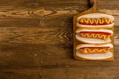 Τρία κλασικά χοτ-ντογκ με το κέτσαπ και τη μουστάρδα Στοκ Εικόνες