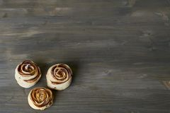 Τρία κομμάτια εύγευστος και γλυκός που ψήθηκε αυξήθηκε διαμορφωμένη ζύμη με την πλήρωση μήλων στην ξύλινη χλεύη υποβάθρου επάνω σ Στοκ Εικόνα