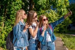 Τρία κορίτσια είναι εφηβικές φίλες Το καλοκαίρι μετά από το σχολείο, στο πάρκο Φωτογραφίες σε ένα smartphone Τζιν ένδυσης στοκ εικόνες