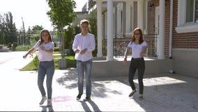 Τρία κορίτσια και το αγόρι έντυσαν στα παρόμοια τζιν και πουκάμισα που χορεύουν στην οδό απόθεμα βίντεο