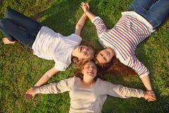 Τρία κορίτσια κρατούν τα χέρια και βρίσκονται στη χλόη στοκ εικόνες με δικαίωμα ελεύθερης χρήσης