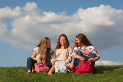 Τρία κορίτσια με τη συνομιλία και το γέλιο τσαντών στη χλόη Στοκ Εικόνες
