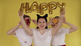 Τρία κορίτσια που έχουν τη διασκέδαση στο κίτρινο υπόβαθρο Τσίχλα, παίζοντας με τις καραμέλες και τα φρούτα απόθεμα βίντεο