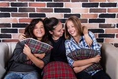 Τρία κορίτσια που αγκαλιάζουν και που χαμογελούν τη συνεδρίαση στον καναπέ Στοκ Φωτογραφία