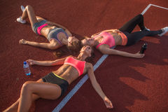 Τρία κορίτσια που βρίσκονται στη χαλάρωση πατωμάτων μετά από να εκπαιδεύσει στοκ φωτογραφίες