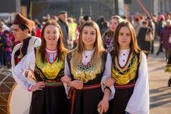Τρία κορίτσια που θέτουν για τη κάμερα στα βουλγαρικά κοστούμια λαογραφίας στοκ εικόνες
