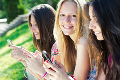Τρία κορίτσια που κουβεντιάζουν με τα smartphones τους Στοκ φωτογραφία με δικαίωμα ελεύθερης χρήσης