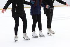 Τρία κορίτσια που κρατούν τα χέρια πάγος-κάνοντας πατινάζ στην αίθουσα παγοδρομίας πάγου Στοκ Φωτογραφίες