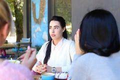 Τρία κορίτσια που μιλούν και κάθονται στον καφέ Όμορφο νέο κορίτσι με το blac Στοκ Εικόνες