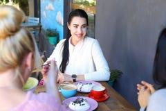 Τρία κορίτσια που μιλούν και κάθονται στον καφέ Όμορφο νέο κορίτσι με το blac Στοκ εικόνες με δικαίωμα ελεύθερης χρήσης