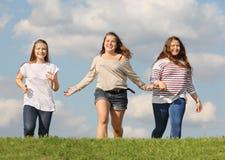 Τρία κορίτσια που οργανώνονται στη χλόη και το χαμόγελο Στοκ φωτογραφία με δικαίωμα ελεύθερης χρήσης