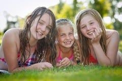 Τρία κορίτσια που χαμογελούν σε ένα λιβάδι στοκ φωτογραφία με δικαίωμα ελεύθερης χρήσης