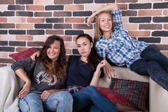 Τρία κορίτσια που χαμογελούν τη συνεδρίαση στον καναπέ Στοκ εικόνες με δικαίωμα ελεύθερης χρήσης