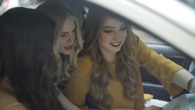Τρία κορίτσια στα αυτοκίνητα σχεδιάζουν τη διαδρομή του ταξιδιού τους με έναν χάρτη απόθεμα βίντεο
