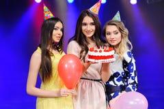 Τρία κορίτσια στα εορταστικά καπέλα και τα μπαλόνια και το κέικ υπό εξέταση Στοκ φωτογραφία με δικαίωμα ελεύθερης χρήσης