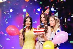 Τρία κορίτσια στα εορταστικά καπέλα και τα μπαλόνια και το κέικ υπό εξέταση Στοκ Εικόνα