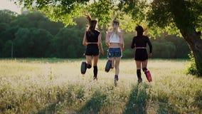 Τρία κορίτσια στις μπότες με την άνοιξη που τρέχει μέσω του θερινού πάρκου στο ηλιοβασίλεμα που κάνει τον αθλητισμό απόθεμα βίντεο