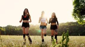 Τρία κορίτσια στις μπότες με την άνοιξη που τρέχει μέσω του θερινού πάρκου στο ηλιοβασίλεμα που κάνει τον αθλητισμό φιλμ μικρού μήκους