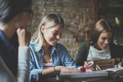 Τρία κορίτσια στον καφέ που έχει τη διασκέδαση στοκ φωτογραφία