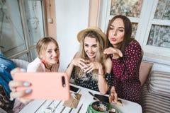 Τρία κορίτσια στον πίνακα στοκ εικόνα