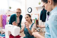 Τρία κορίτσια στο εργοστάσιο ενδυμάτων Επιλέγουν τα κουμπιά για το νέο φόρεμα στοκ φωτογραφίες