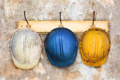 Τρία κράνη κατασκευής που κρεμούν σε μια κρεμάστρα καπέλων Στοκ φωτογραφίες με δικαίωμα ελεύθερης χρήσης
