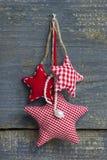 Τρία κόκκινα άσπρα ελεγμένα χειροποίητα αστέρια Χριστουγέννων που κρεμούν στο α Στοκ Φωτογραφία