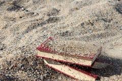 Τρία κόκκινα βιβλία στην άμμο, που καλύφθηκε με την άμμο, έννοια του transience του χρόνου, θόλωσαν το υπόβαθρο Στοκ Εικόνες