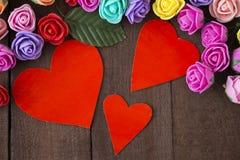 Τρία κόκκινα καρδιές και λουλούδια σε ένα καφετί ξύλο υποβάθρου Στοκ εικόνα με δικαίωμα ελεύθερης χρήσης