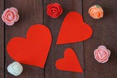 Τρία κόκκινα καρδιές και λουλούδια σε ένα καφετί ξύλο υποβάθρου Στοκ Εικόνες