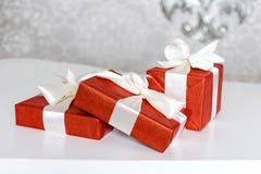Τρία κόκκινα κιβώτια δώρων εορτασμού με τα τόξα κορδελλών στον άσπρο πίνακα Ο σωρός παρουσιάζει στο εσωτερικό πολυτέλειας Στοκ φωτογραφία με δικαίωμα ελεύθερης χρήσης