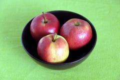 Τρία κόκκινα μήλα μέσα στην πορφυρή κινηματογράφηση σε πρώτο πλάνο κύπελλων Στοκ Εικόνες