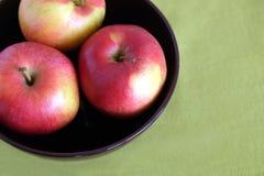 Τρία κόκκινα μήλα μέσα στην πορφυρή κινηματογράφηση σε πρώτο πλάνο κύπελλων Στοκ Φωτογραφία