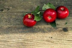 Τρία κόκκινα μήλα σε ένα ξύλινο υπόβαθρο Στοκ Φωτογραφία