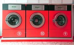 Τρία κόκκινα πλυντήρια στο πλυντήριο νομισμάτων στοκ εικόνες με δικαίωμα ελεύθερης χρήσης