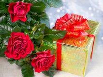 Τρία κόκκινα τριαντάφυλλα και δώρο Στοκ Φωτογραφία