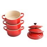 Τρία κόκκινα cocottes με τις καλύψεις σε ένα άσπρο υπόβαθρο Στοκ Εικόνες