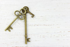 Τρία κλειδιά ορείχαλκου σε ένα άσπρο στενοχωρημένο ξύλινο υπόβαθρο Στοκ Εικόνα