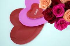 Τρία λαμπρά διαμορφωμένα καρδιά πιάτα και τριαντάφυλλα στη γωνία στοκ εικόνες με δικαίωμα ελεύθερης χρήσης
