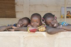 Τρία λατρευτά αφρικανικά παιδιά που θέτουν υπαίθρια το διάστημα αντιγράφων Στοκ Φωτογραφίες
