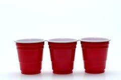 Τρία μίνι κόκκινα φλυτζάνια κατανάλωσης Στοκ φωτογραφία με δικαίωμα ελεύθερης χρήσης