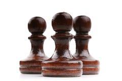 Τρία μαύρα ξύλινα κομμάτια σκακιού μόνο που απομονώνονται στο λευκό Στοκ Εικόνες