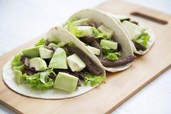 Τρία μεξικάνικα tacos στο μπαμπού επιβιβάζονται σε ένα άσπρο ξύλινο υπόβαθρο, πλάγια όψη στοκ εικόνα με δικαίωμα ελεύθερης χρήσης