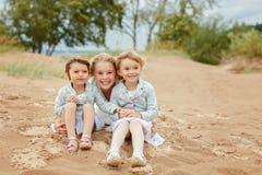 Τρία μικρά κορίτσια είναι λατρευτές αδελφές που αγκαλιάζουν στο backgroun στοκ φωτογραφία με δικαίωμα ελεύθερης χρήσης