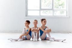 Τρία μικρά κορίτσια μπαλέτου που κάθονται και που θέτουν από κοινού στοκ εικόνες